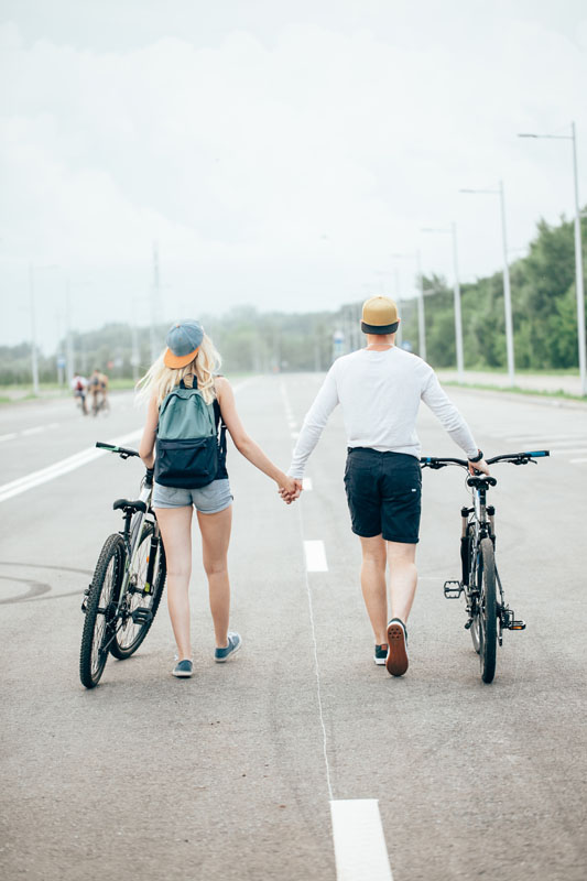 man and woman walk their bikes down the road